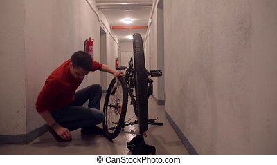 A man repairs a bicycle in the basement of a house