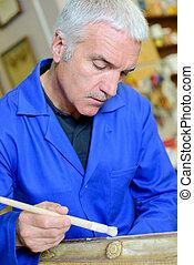 a man restoring an antiquetn?