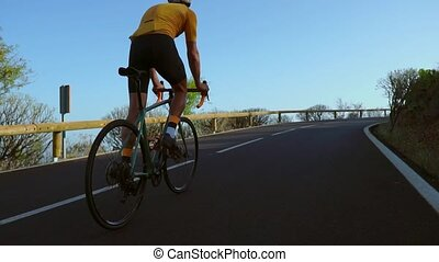 A man ride on bike on the road. Sport and active life concept sunset time. A man riding on bicycle in a park. Blue sky with orange sun beam over the body of cyclist