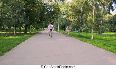 A man rides a bicycle in the park on a sunny day.