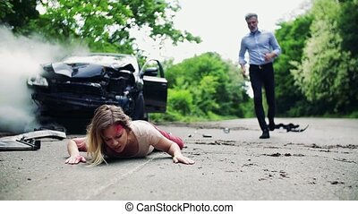 A man running towards a young woman lying on the road after a car accident.