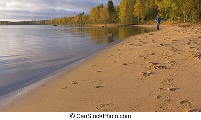 A man runs along the lake on a sandy beach. Early in the morning at dawn. He plays sports and leads a healthy lifestyle.