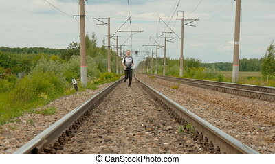 A man runs along the railroad tracks.
