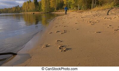 A man runs along the sandy beach. Early in the morning at...