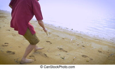 A man runs up to the waters edge and draws a dollar sign in the sand