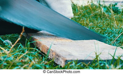 A man sawing wood Board with hand saw - Man sawing wood...