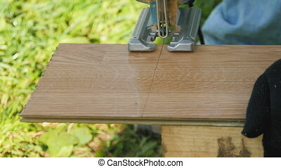 A man saws a laminate with an electric jigsaw. close-up