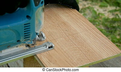 A man saws a laminate with an electric jigsaw. Makes repairs...