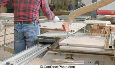 a man saws wooden door blanks on the machine, the production of village interior doors