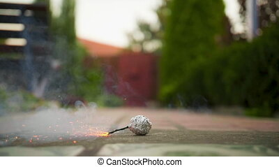 A man set fire a bomb in slow motion outdoors.