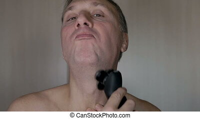 A man shaves his face, a modern electric razor. Slow motion...