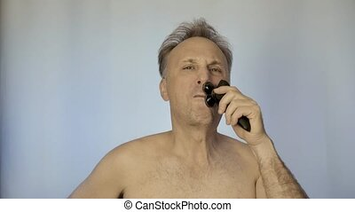A man shaves with an electric razor. In the morning in front of the mirror. He looks after his appearance.
