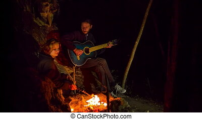A man sings a serinade to a girl near the fire