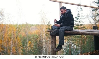 A man sits at a high altitude and eating the canned food...