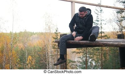 A man sits at a high altitude and opens the canned food with...