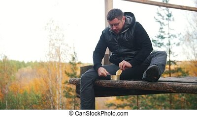 A man sits at a very high altitude and opens the canned food...