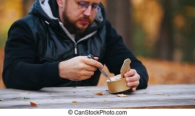 A man sits at the table and eating canned stewed meat using...