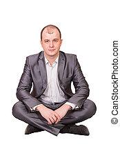 A man sits cross-legged