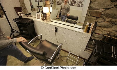 A man sits down on a Chair in a hair salon - Young man sits...