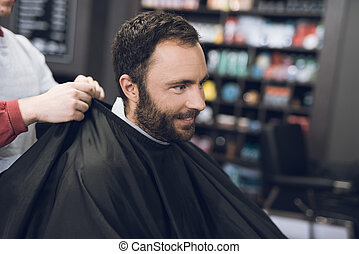A man sits in a barber's chair in a man's barbershop, where he came to cut his hair.