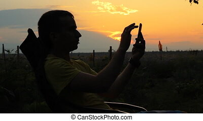 A man sits in a chair with the phone. Against the background of an orange sky after sunset