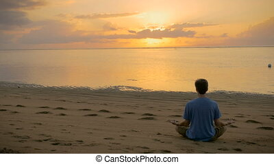 A man sits in a lotus pose facing the ocean during sunrise -...
