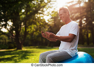 A man sits on a ball for yoga and looks at something on his tablet. He smiles