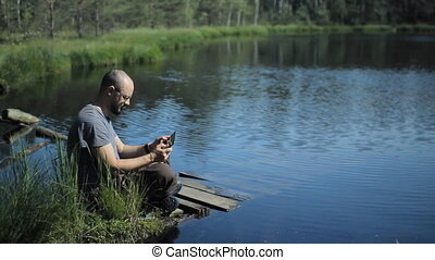 A man sits on a pier of the lake and play on tablet in game. The beautiful blue lake and forest on background