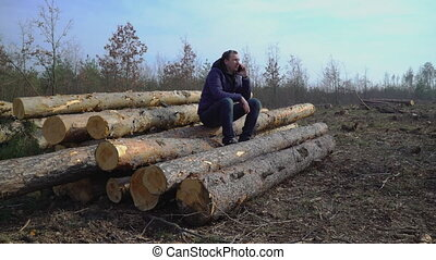 A man sits on logs and calls by phone when ordering a car for transporting timber