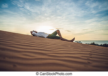 A man sits on the sand in the desert