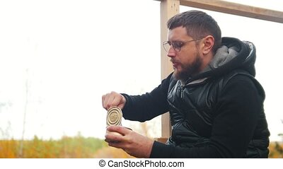 A man sits outdoors and eating the canned food with a knife....