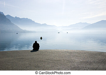 A man sitting at edge of the lake of annecy, in front of mountains on morning. France