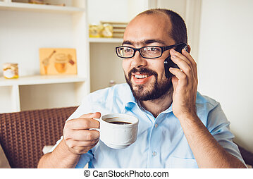 a man sitting in a cafe talking on mobile and drinking coffee