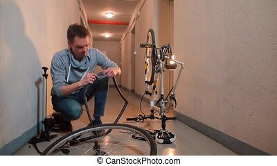 A man sitting in a garage looking for a hole in the rubber of a bicycle wheel.