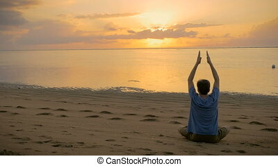 A man sitting in a lotus yoga pose at ocean lowering arms...