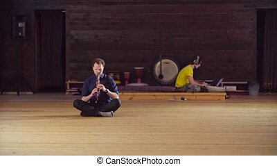 A man sitting on the floor and playing flute