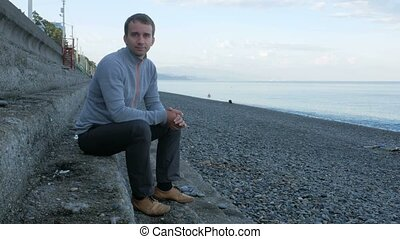 A man sitting on the steps near the pebble beach of the ocean. He looks at the camera and smiling