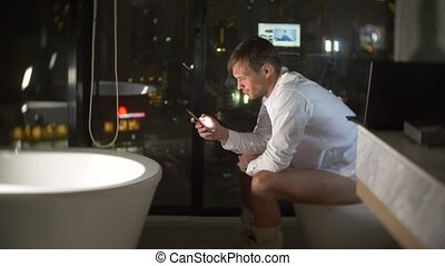 A man sitting on the toilet in a luxurious restroom with a...