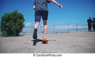 A man skating on a penny board on the quay. Mid shot