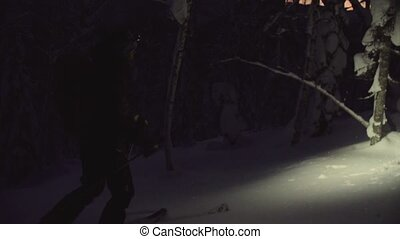 A man skiing in a night snowy forest with a flashlight