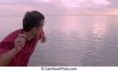 A man skipping stones into a clam ocean on the beach - A man...
