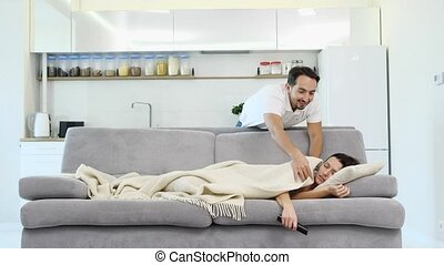 A man sleeps on the floor while his wife watches a TV