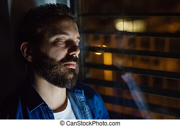A man slepping by the window at home at night.