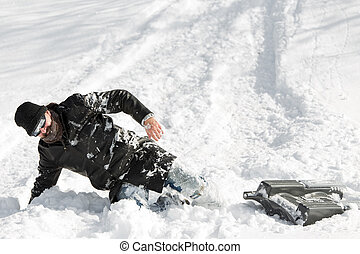 man slumping in the deep snow after a sleigh ride with a sledge