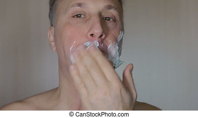 A man smears his face with shaving foam. Close-up.