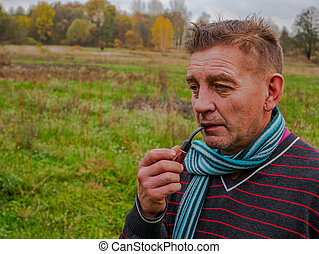 A man smokes a tobacco pipe in the street.