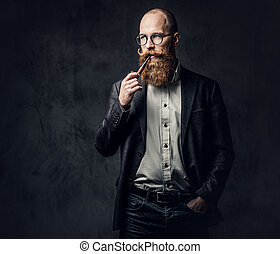Redhead bearded male dressed in a suit and eyeglasses smoking tradition pipe over dark grey background.
