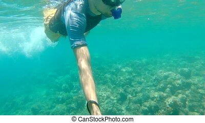 A man snorkeling in a clear blue sea