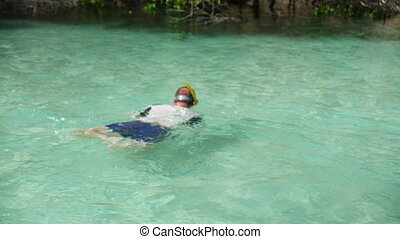 A man snorkeling in a turquoise water - Shot of a man...
