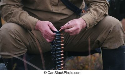 A man soldier prepares the ammunition for the charge in the machine gun. Mid shot